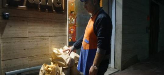 Homem pegando alimentos - Padeiro deixa à noite vários saquinhos de pães que não vendeu de dia em um banco para alimentar pessoas carentes.