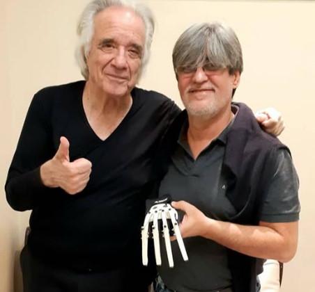 O maestro com o designer Ubiratan Bizarro Foto Facebook - Maestro João Carlos Martins voltou a tocar neste Natal após ganhar luvas biônicas.