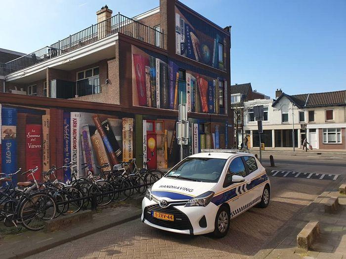 Bv3ewlihLyd png  700 - Artistas holandeses pintam estante gigante em um prédio de apartamentos com os livros favoritos dos moradores