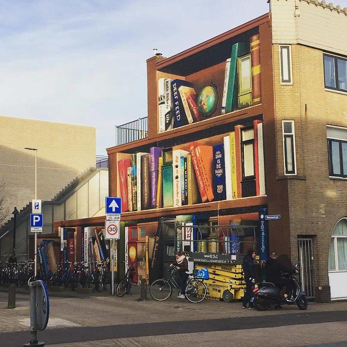 BvXIxy lQPO png  700 - Artistas holandeses pintam estante gigante em um prédio de apartamentos com os livros favoritos dos moradores
