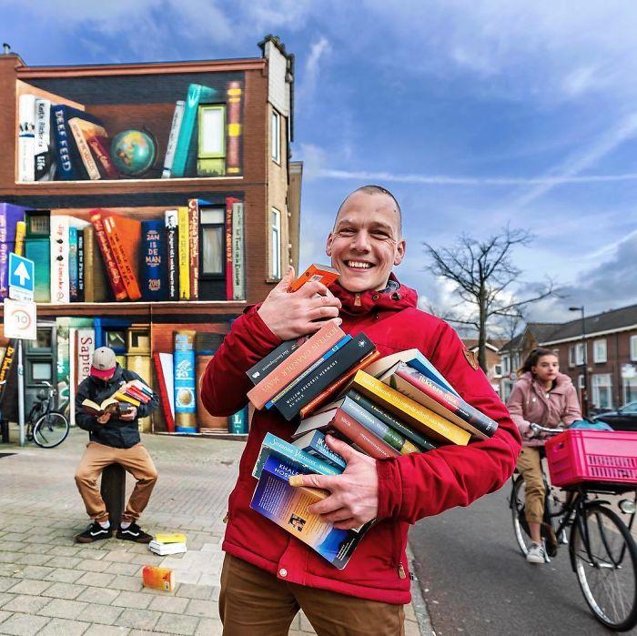 BvjK3UflMzU png  700 - Artistas holandeses pintam estante gigante em um prédio de apartamentos com os livros favoritos dos moradores