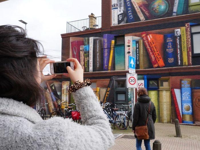 street art utrecht apartment building transformed into bookcase jan is de man 5cadbde1ea71e  700 - Artistas holandeses pintam estante gigante em um prédio de apartamentos com os livros favoritos dos moradores
