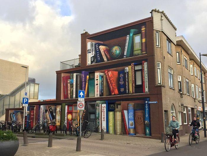 street art utrecht apartment building transformed into bookcase jan is de man 5cadbde50cee4  700 1 - Artistas holandeses pintam estante gigante em um prédio de apartamentos com os livros favoritos dos moradores