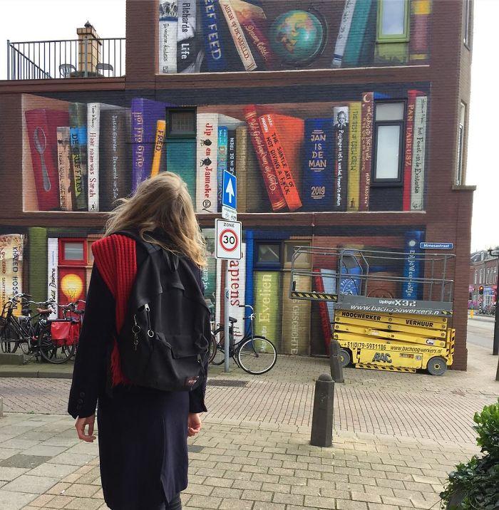 street art utrecht apartment building transformed into bookcase jan is de man 5cadbde82a926  700 - Artistas holandeses pintam estante gigante em um prédio de apartamentos com os livros favoritos dos moradores