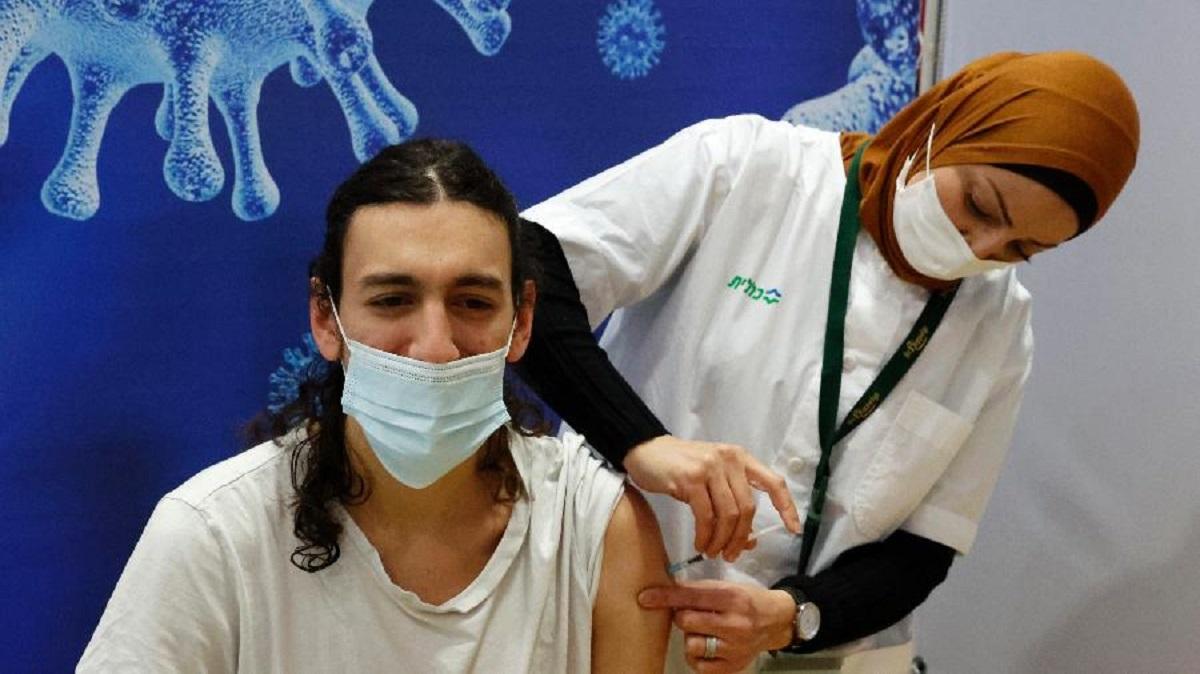 4jan2021 profissional da saude aplica vacina contra covid 19 da pfizerbiontech em jovem na cidade hod hasharon em israel 1612457991251 v2 900x506 - Israel inicia vacina em massa de todos os cidadãos acima de 16 anos contra Covid-19