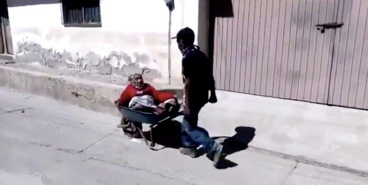 a 4 - Vídeo mostra filho carregando sua mãe de 100 anos em um carrinho de mão para vaciná-la.